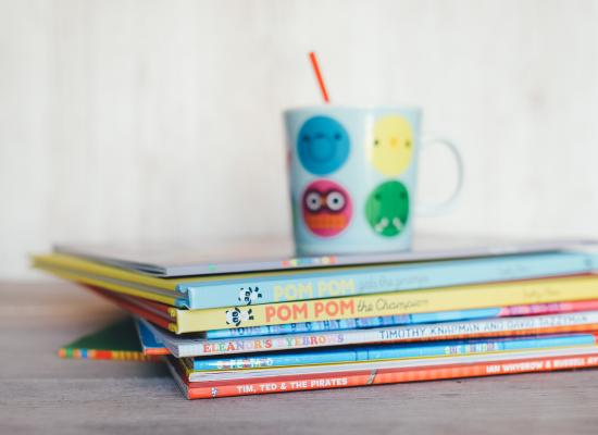stack of childrens books and a mug