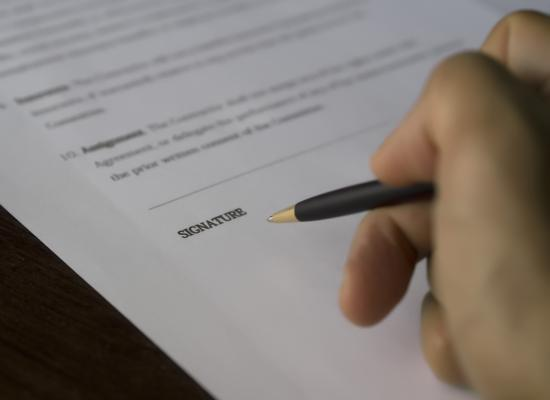 hand with pen signing a document