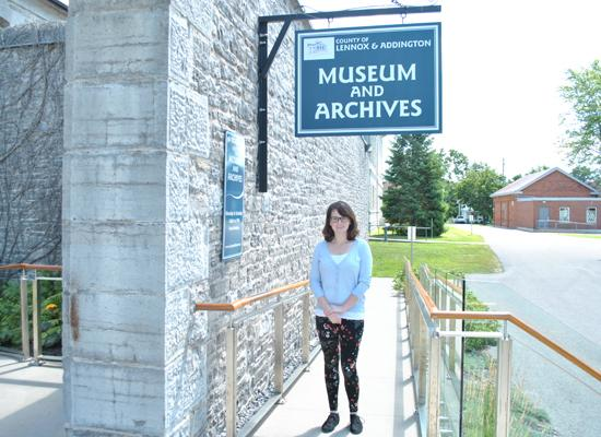 girl outside under museum sign